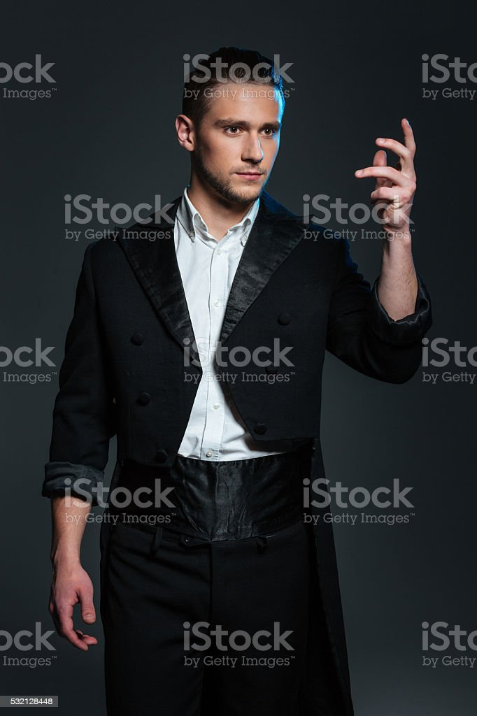 Serious young man magician in black tail coat showing tricks stock photo