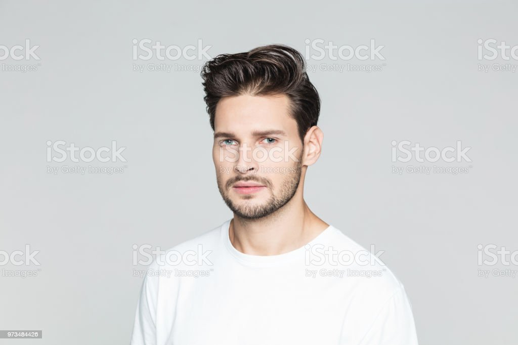 Serious young man on grey background Portrait of serious young man with beard standing on grey background 25-29 Years Stock Photo