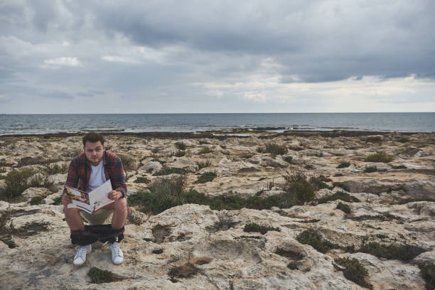 serieuze jonge man lezen magazine op toilet - newspaper beach stockfoto's en -beelden