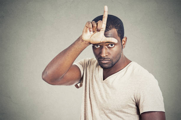 serious young man showing loser sign on forehead Closeup portrait serious young man showing loser sign on forehead looking at you with disgust at camera isolated grey wall background. Negative human emotion facial expression feeling antagonize stock pictures, royalty-free photos & images