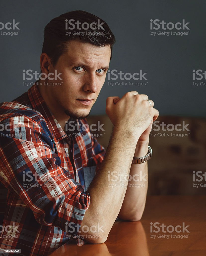 Serious young man sitting at the table stock photo