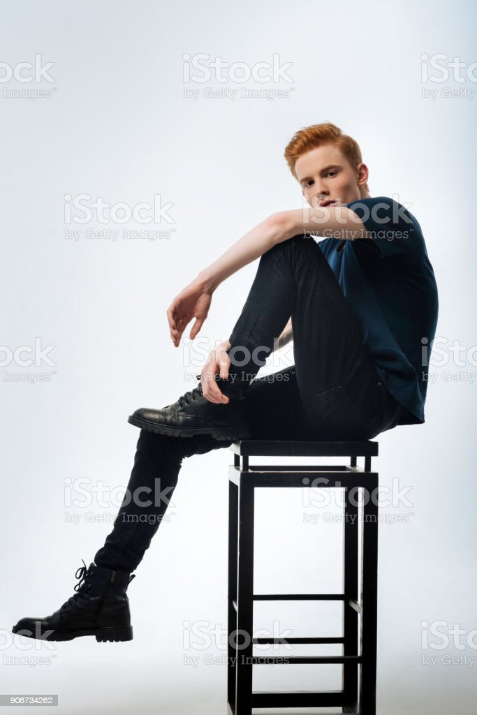 Serious young man sitting on the chair stock photo