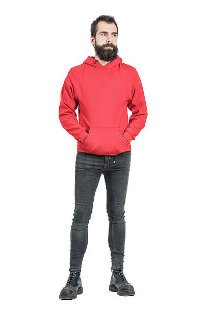 Serious young punker in red hooded sweatshirt looking away Serious young punker in red hooded sweatshirt looking away. Full body length portrait isolated over white studio background. men in tight jeans stock pictures, royalty-free photos & images