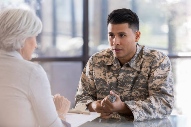 Serious young soldier discusses issues with counselor stock photo