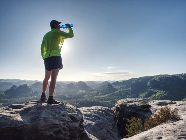Serious young sportsman breathing and drinking water stock photo