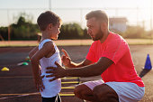 istock Serious young trainer giving lecture to a little boy because of his bad acting on training. 1034892896