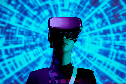 Serious young woman immersed into augmented reality using virtual reality simulator against digital background
