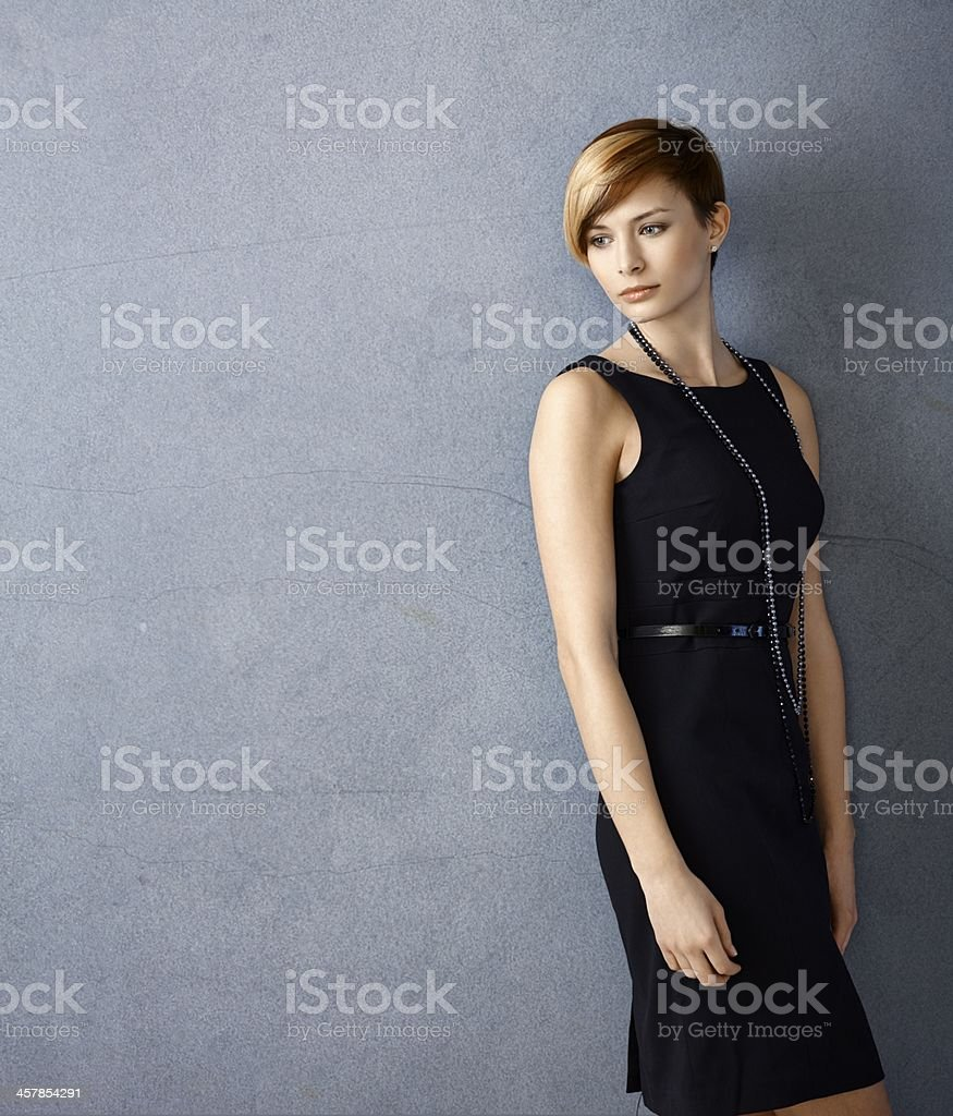 Serious young woman in black dress stock photo