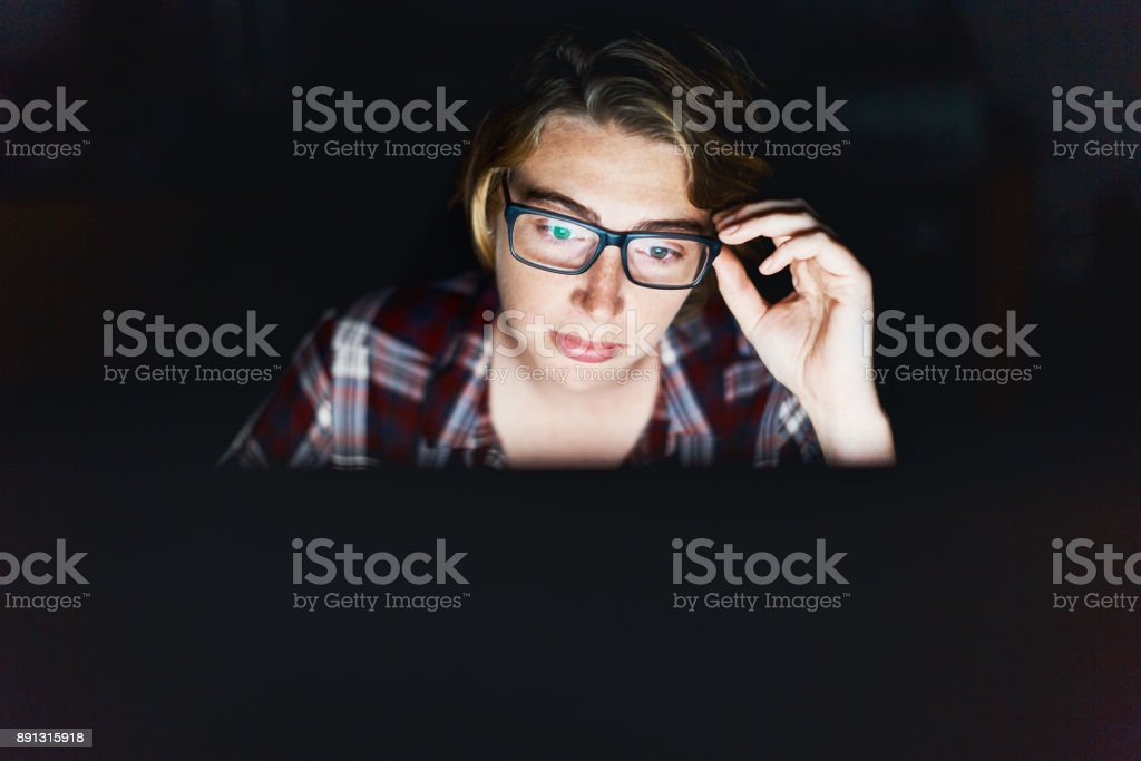 Serious young woman, lit by monitor against black, adjusts spectacles stock photo