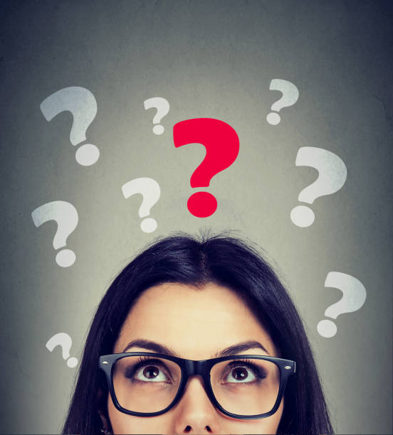 Serious young woman looking up at key question stock photo