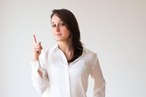 ernste junge frau index zeigefinger oben - spielerfrauen stock-fotos und bilder