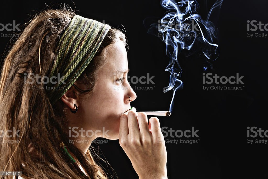 Serious young woman puffs on a marijuana reefer stock photo