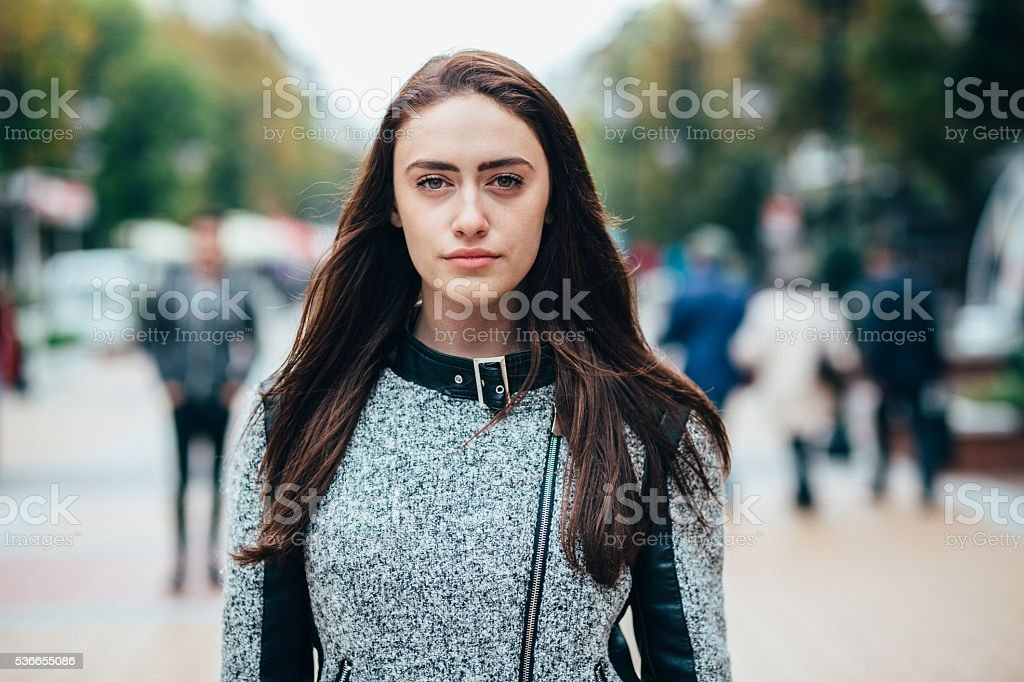Serious young woman standing on the street stock photo