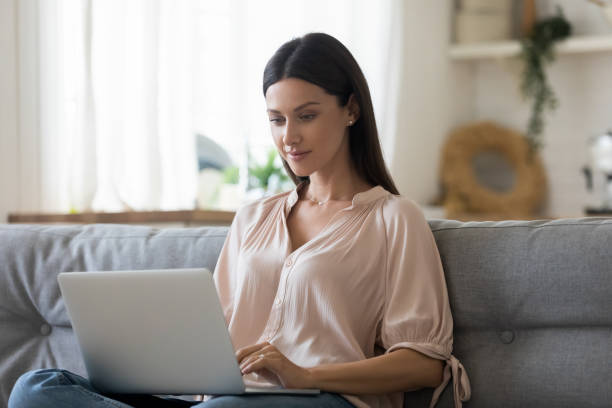 Serious young woman using laptop at home, looking at screen stock photo