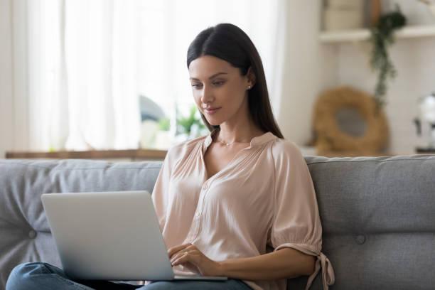 Ernsthafte junge Frau mit Laptop zu Hause, Blick auf den Bildschirm – Foto