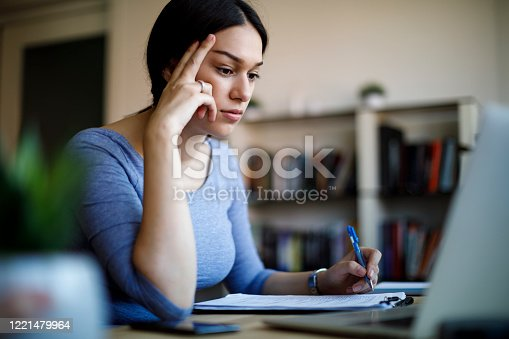 1057767656 istock photo Serious young woman working from home 1221479964