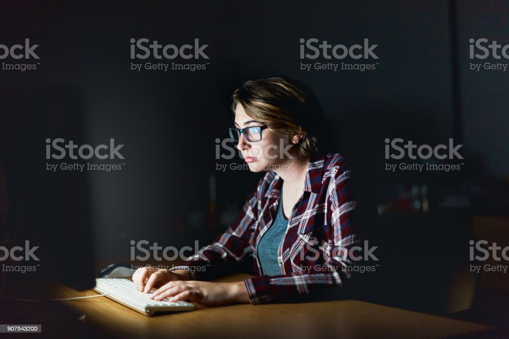 A young woman in spectacles concentrates as she works on her computer...