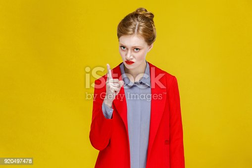 istock Seriously angry woman in red suit attention you. 920497478