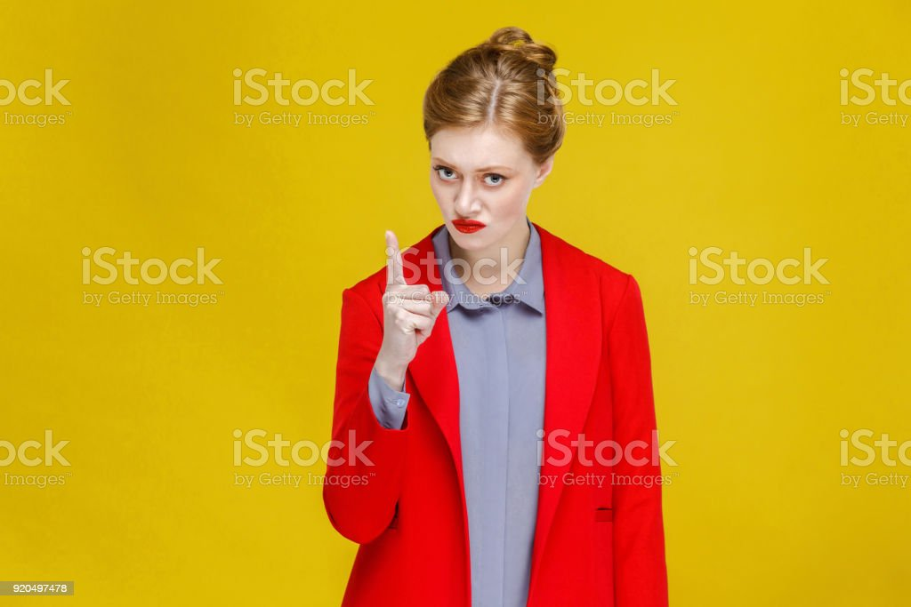 Seriously angry woman in red suit attention you. stock photo