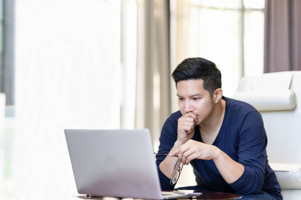 serieus vertrouwen aziatische jonge freelancer in de smart casual arbeids- en geconcentreerd op laptop zitten op balie in moderne kantoor, mede werkruimte of op huis met kopie ruimte, webinar via het internet - achterdocht stockfoto's en -beelden