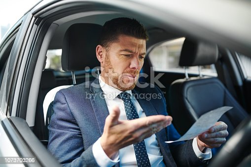 Cropped shot of a handsome mature businessman looking at his parking ticket while sitting in the driver's seat of his car