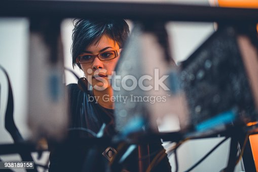Young woman repairing boards and checking the cables so she could do her crypto mining at its best
