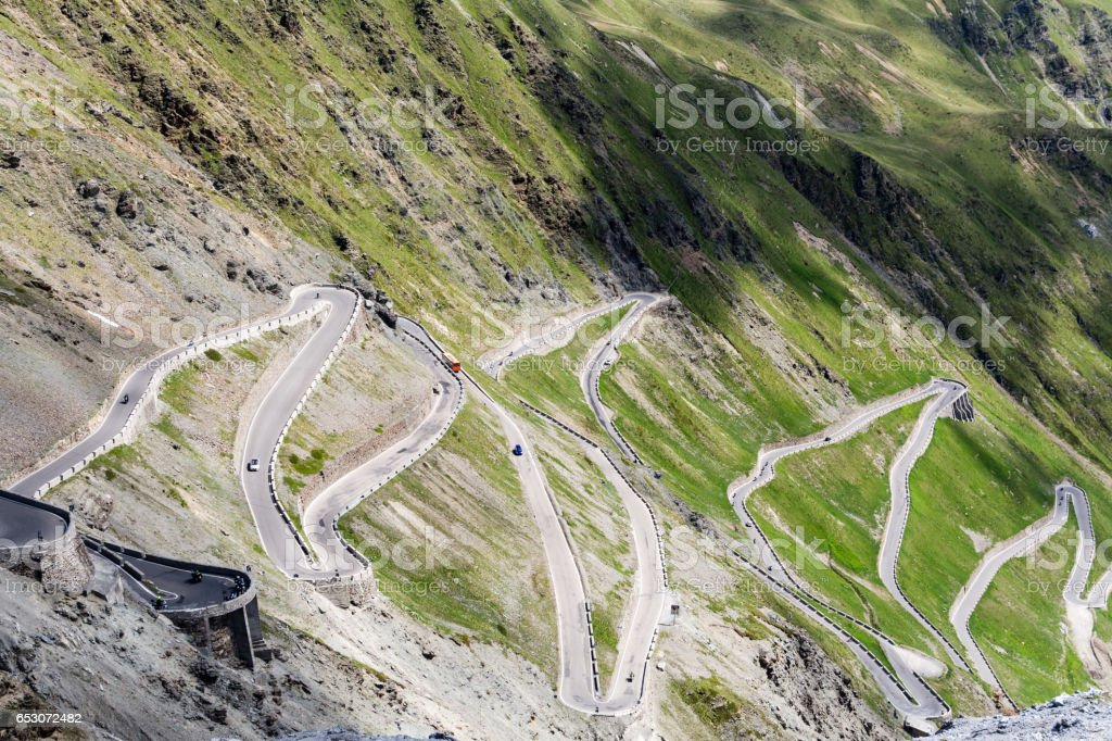 Serpentine mountain road surrounded by green hills. stock photo