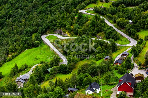 Narrow serpentine road among the small mountain Norwegian village.