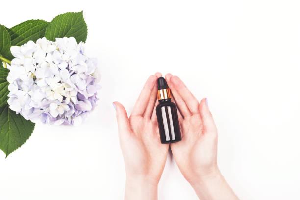 Serumflasche oder ätherisches Öl in den Händen der Frau. – Foto