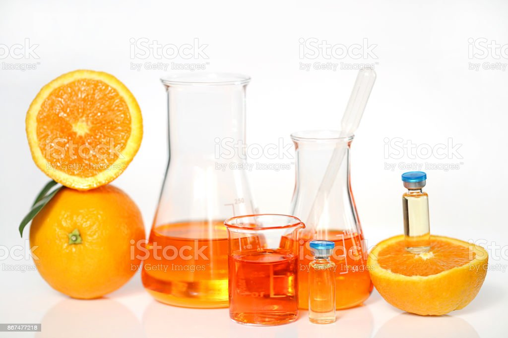 Serum with vitamin C in ampoules. vitamin c in laboratory bottles, orange in a cut on a white background. Vitamins concept. Organic vegan cosmetics for beauty and health. stock photo
