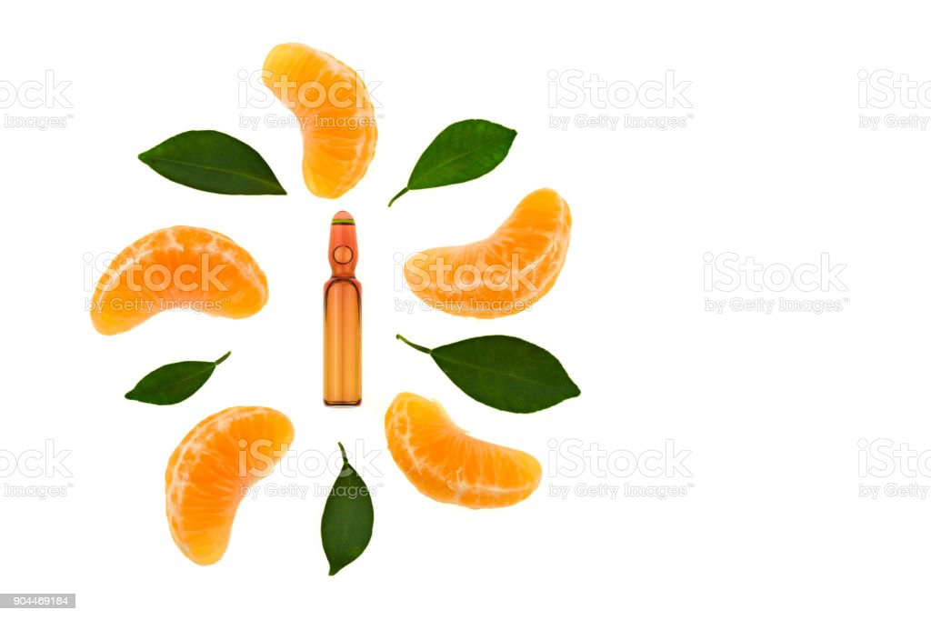 Serum with Vitamin C. One brown ampoule of vitamin C, slices and leaves of mandarin isolated on a white background. Health and Beauty stock photo