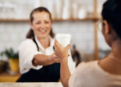 Shot of a barista handing a customer a cup of coffee at a cafe