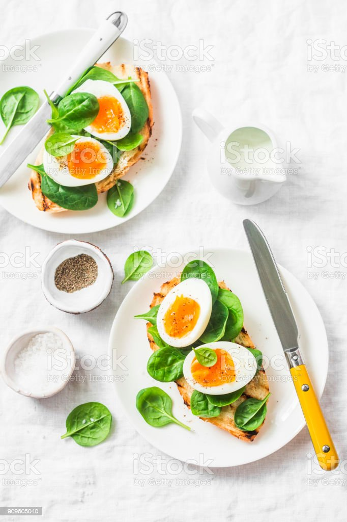 Served Easter brunch plate - grilled bread sandwich with spinach and boiled eggs on white background, top view stock photo