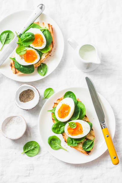 served easter brunch plate - grilled bread sandwich with spinach and boiled eggs on white background, top view - easter brunch stock photos and pictures
