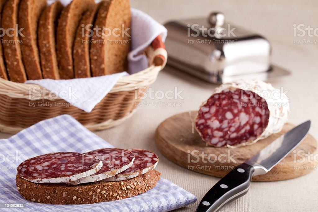 Served kitchen table, sandwich on napkin, salami, breadbasket, s royalty-free stock photo