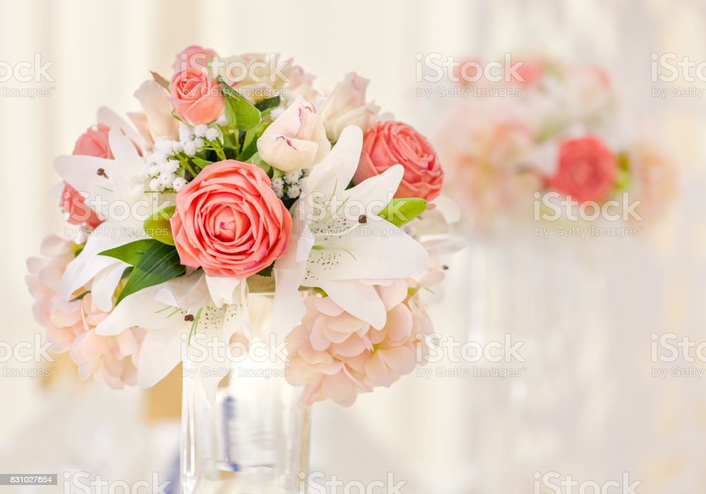Served table for event dinner, decorated with floral compositions in vases in pink and coral shades. Wedding bouquet stock photo