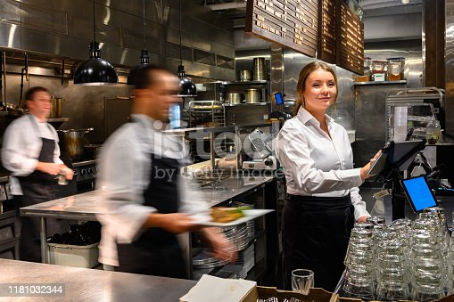 Waitress with a digital tablet. Foodservice and hospitality workers. Restaurant staff working.