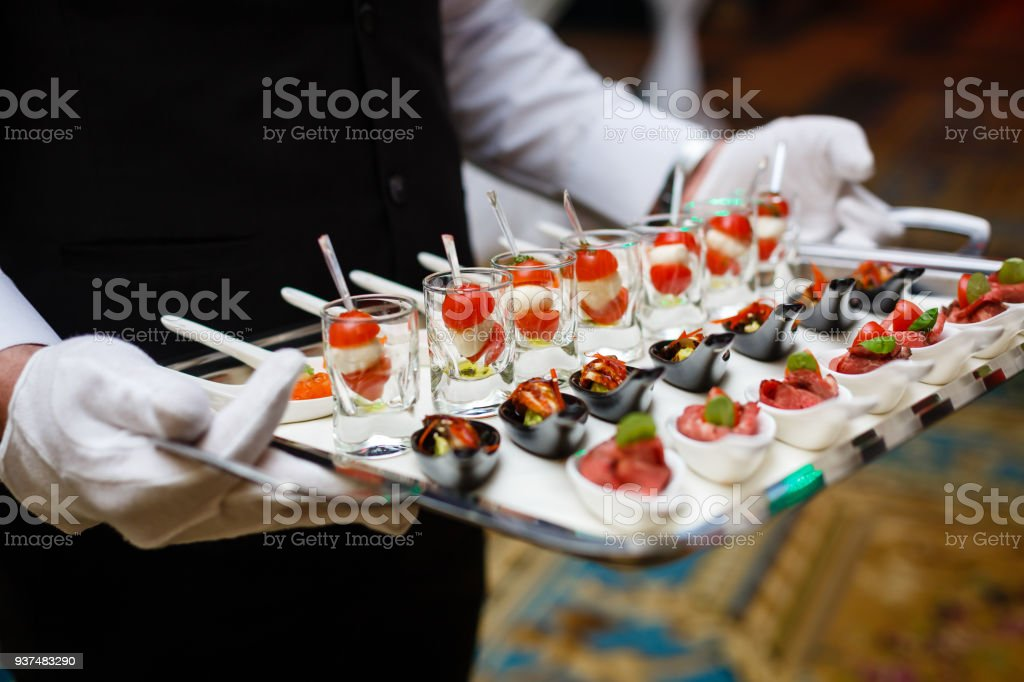 Server holding a tray of appetizers at a banquet - foto stock