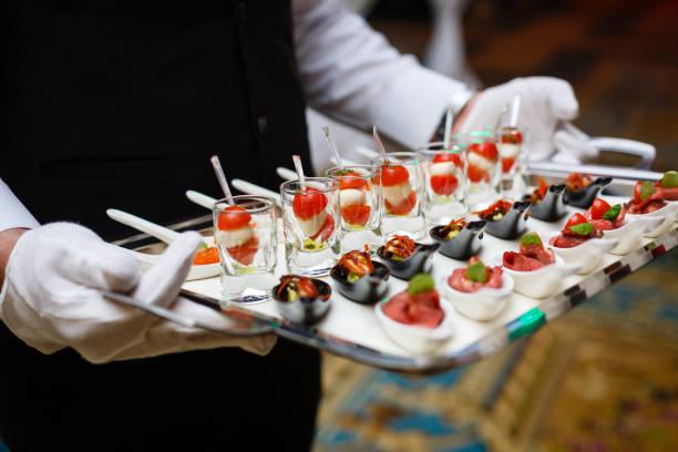Serveur qui détient un plateau d'amuse-bouche lors d'un banquet - Photo