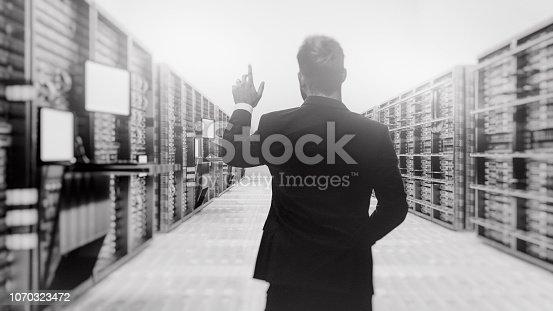 802303672 istock photo Server room with businessman 1070323472