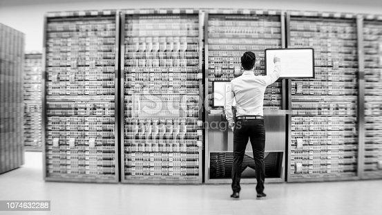 802303672istockphoto Server room with businessman 1074632288