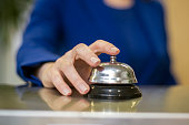 A woman ringing a call bell at a hotel lobby or reception desk. Unrecognizable Caucasian female.