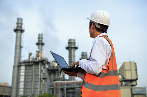 Service engineer is working at electric power plant with laptop