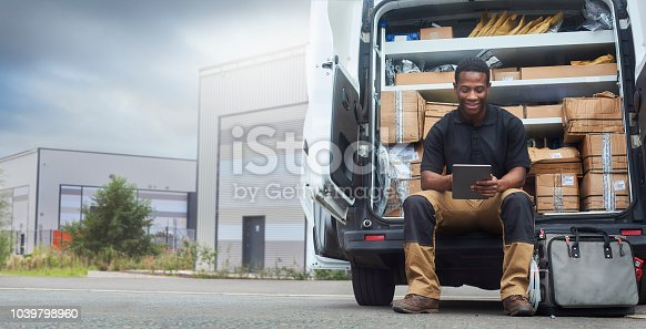 A service engineer sat at the back of his van using a digital tablet outside factory buildings