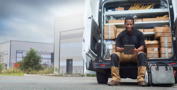 Service engineer sat at the back of his van A service engineer sat at the back of his van using a digital tablet outside factory buildings delivery man stock pictures, royalty-free photos & images