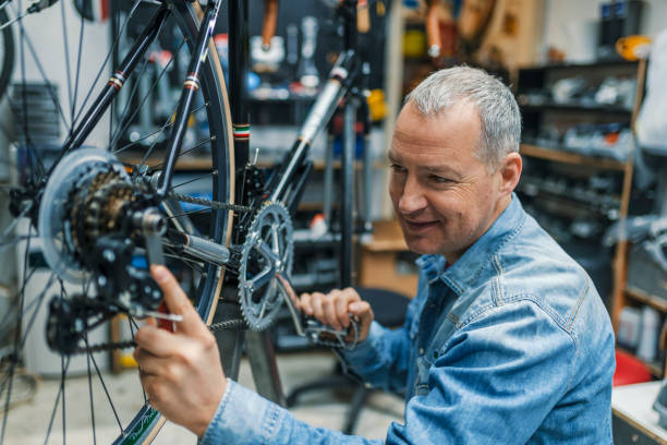 Service for bike with adept repairing bike Service for bike with adept repairing bike. Bicycle mechanic in a workshop in the repair process. Stylish bicycle mechanic doing his professional work in workshop. bicycle shop stock pictures, royalty-free photos & images
