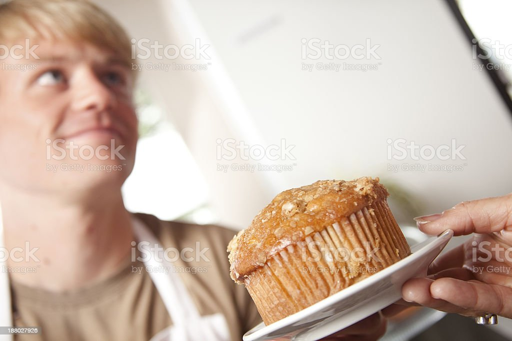 Service Industry: Baker serves a muffin at local bakery. stock photo