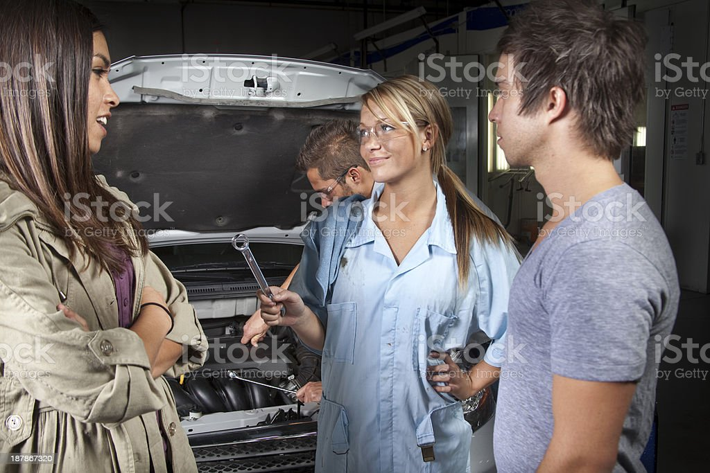 Service Industry: Couple discusses vehicle repairs with mechanic. royalty-free stock photo