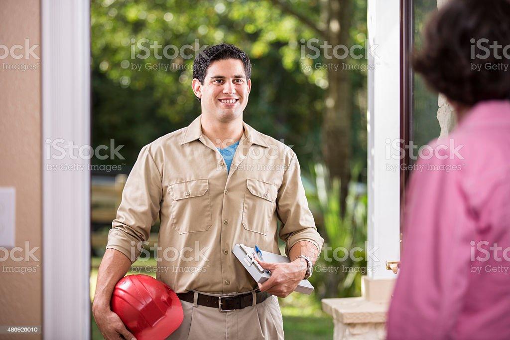 Service Industry: Latin descent repairman at customer's front door. stock photo