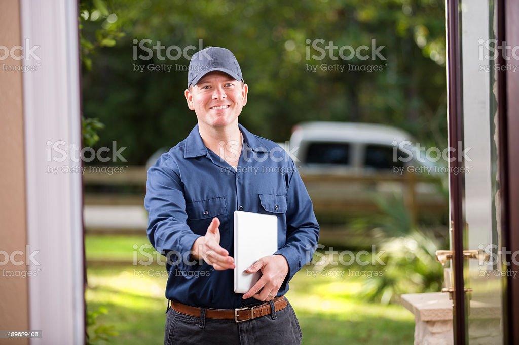 Service Industry: Repairman at customer's front door. Digital tablet. Handshake. stock photo